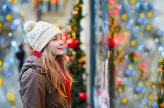 Girl on a Parisian street or at Christmas market looking at shop windows decorated for Christmas